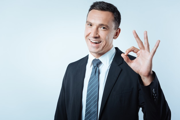 Empresário de sucesso. homem bom e alegre mostrando um gesto de ok e se sentindo feliz por ser um empresário de sucesso