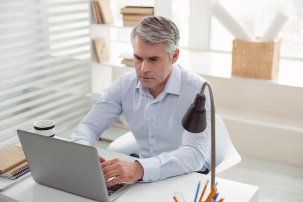 Empresário de sucesso. homem bonito sério sério sentado no escritório e trabalhando no laptop enquanto é um empresário de sucesso