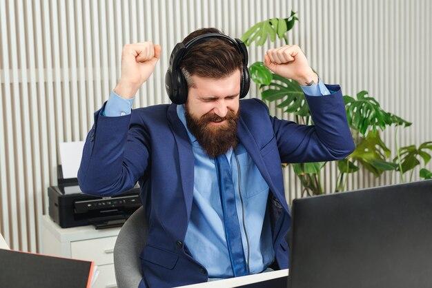 Empresário de sucesso levantou as mãos para comemorar sua vitória. homem vencedor feliz sentado na mesa do escritório. homem de negócios barbudo gritando sim. homem comemorando o sucesso nos negócios.