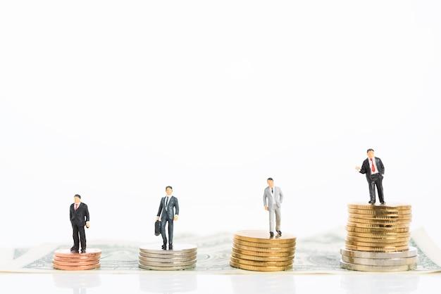 Empresário de sucesso miniture em terno preto trabalho em equipe fica em pé sobre moedas de ouro e prata isoladas no branco