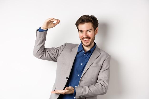 Empresário de sucesso mostrando tamanho grande, forma de objeto grande e sorrindo satisfeito