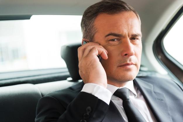 Empresário de sucesso no carro. homem de negócios maduro e confiante falando ao celular e desviando o olhar enquanto está sentado no banco de trás de um carro
