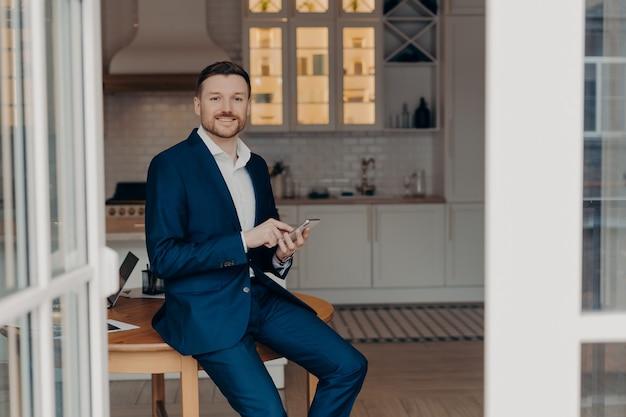 Empresário de sucesso no terno digitando mensagem no celular ou lendo notícias e sorrindo para a câmera enquanto se inclina sobre a mesa de madeira na sala de estar de seu apartamento moderno. conceito de pessoas de negócios