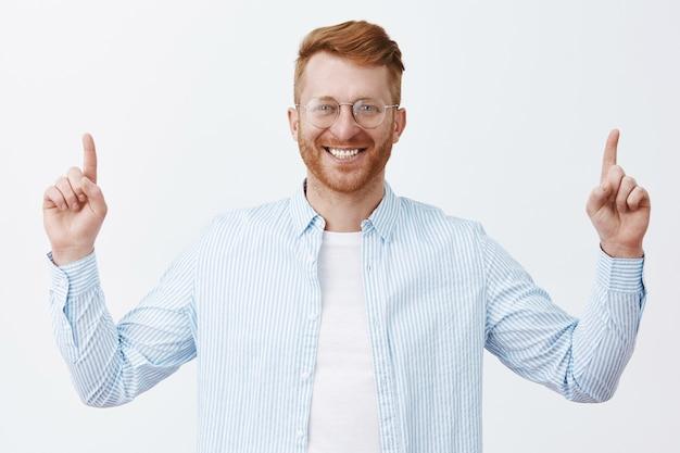 Empresário de sucesso pronto para chegar ao topo do sucesso. retrato de um homem ruivo encantador, satisfeito e despreocupado, com barba de óculos e camisa levantando as mãos, apontando para cima e sorrindo amplamente
