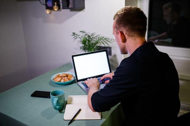 Empresário de sucesso, retrovisor, sentado à mesa em casa, olhando para a tela de um laptop, sente-se satisfeito com o orgulho pelo trabalho realizado, homem sereno trabalha, mãos atrás da cabeça, trabalho em casa