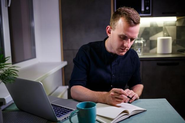 Empresário de sucesso sentado à mesa em casa, olhando para a tela de um laptop, sente-se satisfeito com o orgulho pelo trabalho realizado, homem sereno trabalha, mãos atrás da cabeça, trabalho em casa