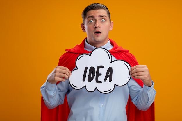 Empresário de super-herói com capa vermelha segurando um cartaz de bolha do discurso com a ideia da palavra, olhando para a câmera espantado e surpreso em pé sobre um fundo laranja