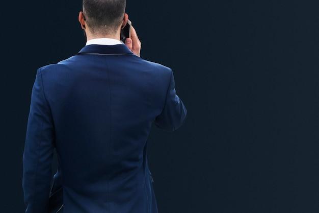 Empresário de terno azul falando ao telefone