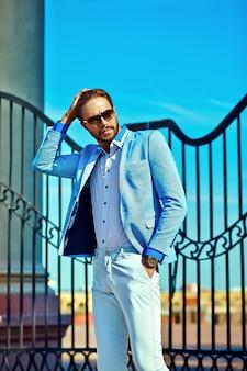 Empresário de terno azul, usando óculos escuros na rua