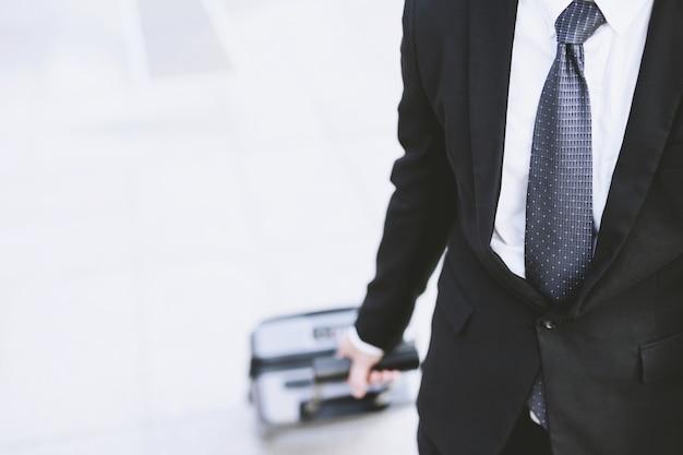Empresário de terno caminhando do lado de fora do prédio de transporte público com bagagem na hora do rush
