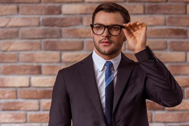 Empresário de terno clássico e óculos.