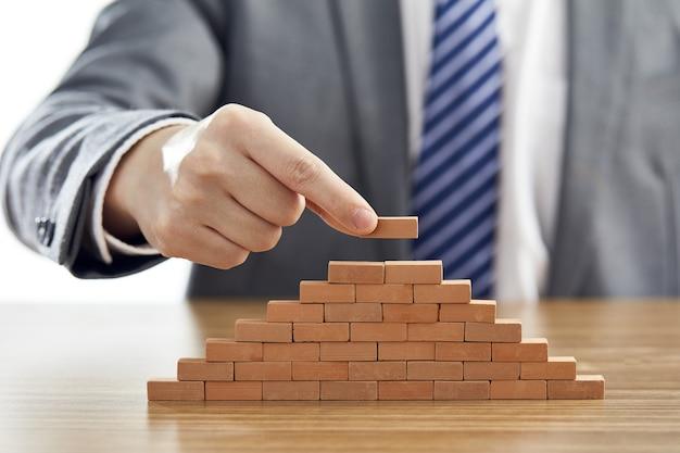 Empresário de terno colocando a última peça de uma pirâmide usando blocos de madeira
