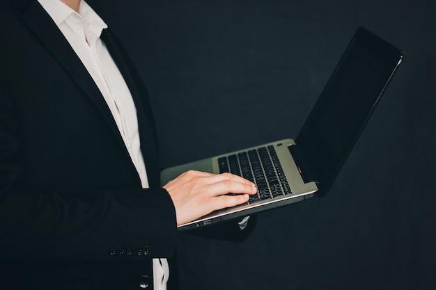 Empresário de terno com um laptop nas mãos. homem com laptop nas mãos