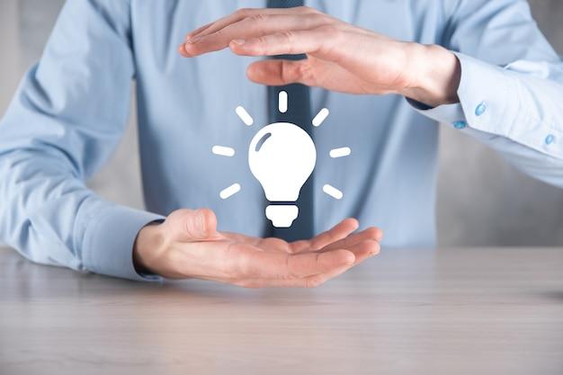 Empresário de terno com uma lâmpada nas mãos. tem um ícone de ideia brilhante na mão. com um lugar para texto.