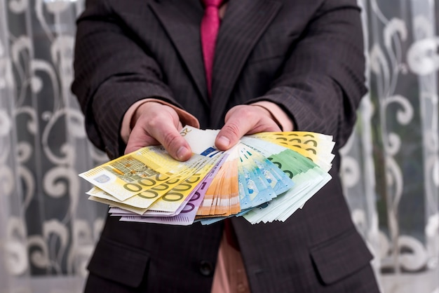 Empresário de terno com ventilador de notas de euro