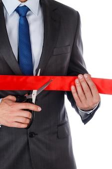 Empresário de terno cortando a fita vermelha com uma tesoura