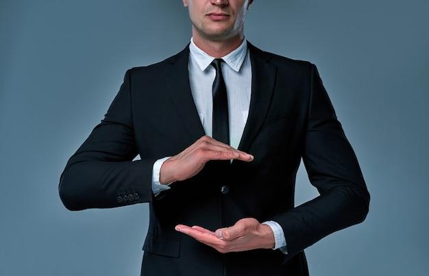Empresário de terno e gravata com a mão estendida para implementação de gráfico futurista. conceito: negócio, gráfico, holografia, canal alfa.