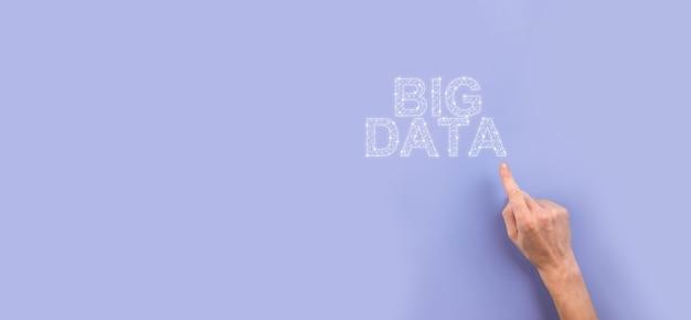 Empresário de terno em um fundo escuro mantém a inscrição big data. conceito de servidor online de rede de armazenamento. rede social ou representação analítica de negócios