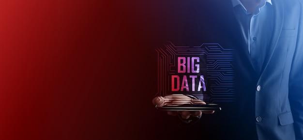 Empresário de terno em um fundo escuro mantém a inscrição big data. conceito de servidor online de rede de armazenamento. rede social ou representação de análise de negócios