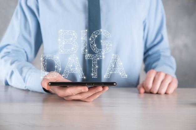Empresário de terno em um fundo escuro mantém a inscrição big data. conceito de servidor online de rede de armazenamento.