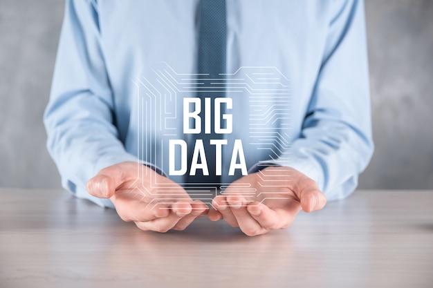 Empresário de terno em um fundo escuro mantém a inscrição big data.