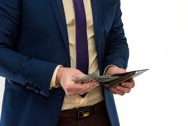 Empresário de terno nos tira dinheiro da carteira, isolado. mãos masculinas segurando uma carteira de couro preto com dinheiro de dólares americanos dentro. conceito de negócios, finanças e dinheiro