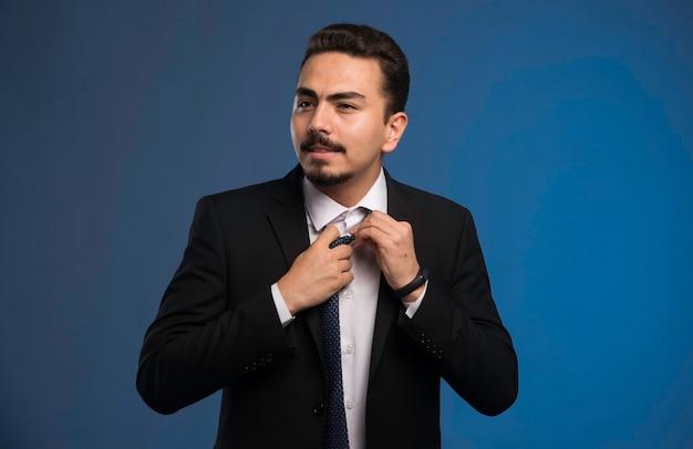 Empresário de terno preto abrindo o botão da camisa.