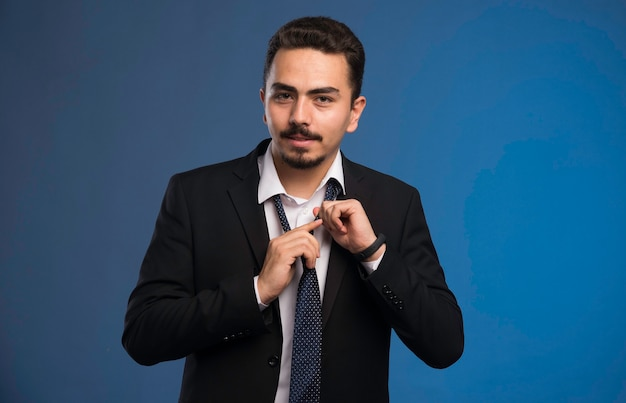 Empresário de terno preto, amarrando uma gravata.