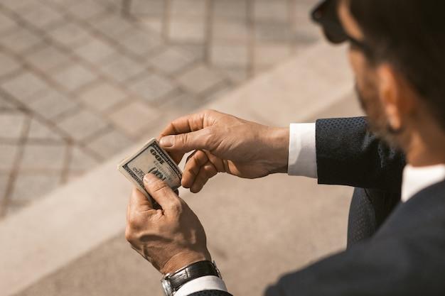 Empresário de terno preto com cerdas e óculos contando os honorários em dólares enquanto está sentado
