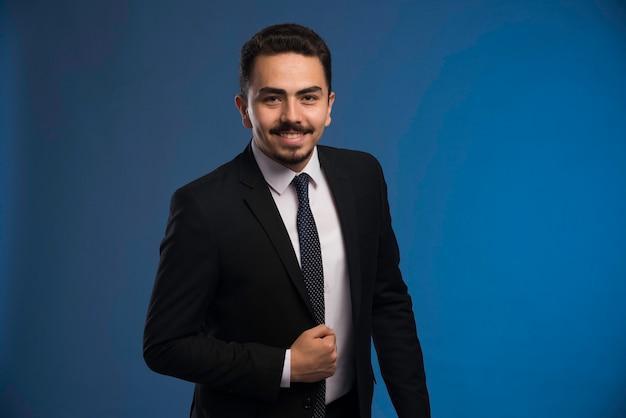 Empresário de terno preto com uma gravata posando.