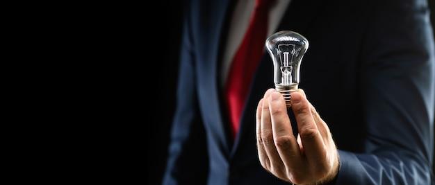 Empresário de terno preto com uma lâmpada na mão em um fundo preto com espaço de cópia