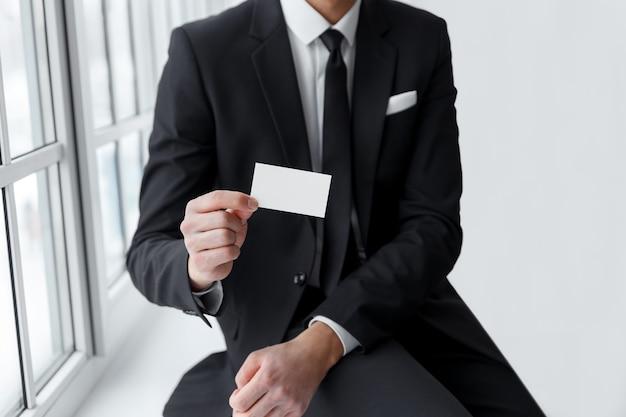 Empresário de terno preto mostrando um cartão