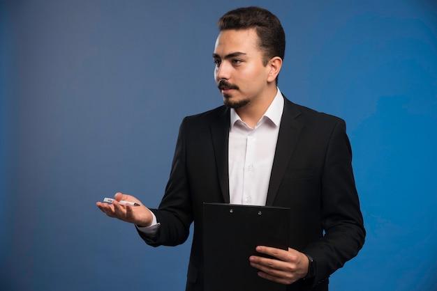 Empresário de terno preto segurando a lista de tarefas e pedindo relatório.