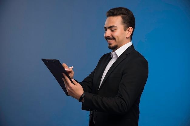 Empresário de terno preto segurando a lista de tarefas e tomando notas.