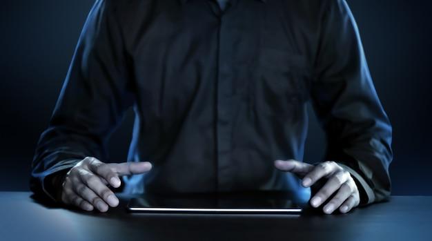 Empresário de terno preto, sentado com um tablet com uma tela em branco.