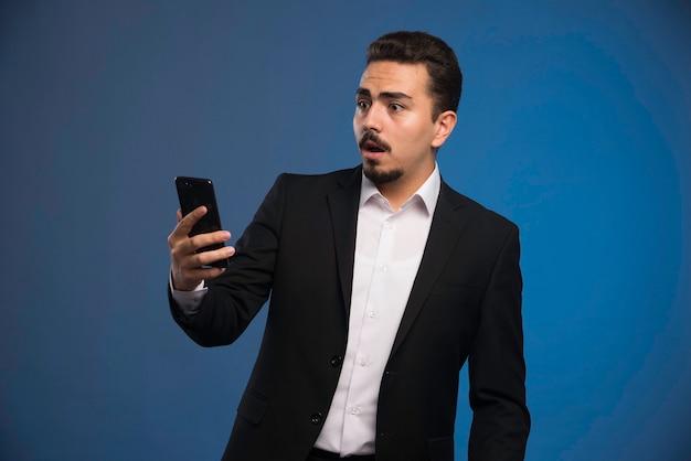 Empresário de terno preto verificando o telefone e surpreso.