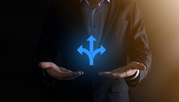 Empresário de terno segura uma placa mostrando três direções em dúvida tendo que escolher entre três opções diferentes indicadas por setas apontando na direção oposta conceito três maneiras de escolher