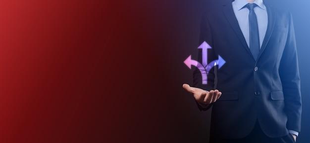 Empresário de terno segura uma placa mostrando três direções. na dúvida, ter que escolher entre três opções diferentes indicadas por setas apontando no conceito de direção oposta. três maneiras de escolher