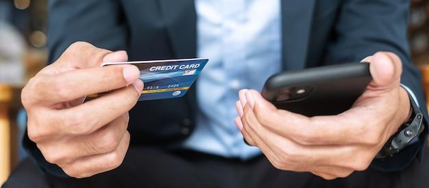 Empresário de terno segurando cartão de crédito e usando smartphone touchscreen para compras online enquanto faz pedidos no café ou no escritório. conceito de negócio, tecnologia, comércio eletrônico e pagamento online