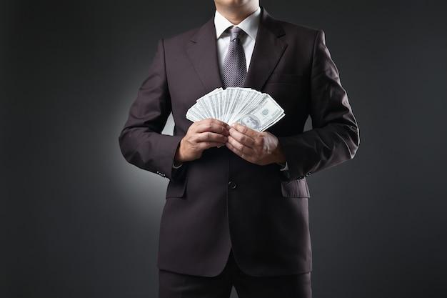 Empresário de terno segurando dinheiro nas mãos em fundo escuro