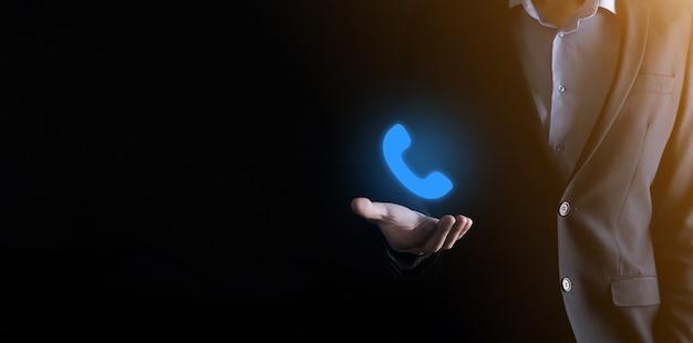 Empresário de terno segurando ícone de telefone holográfico