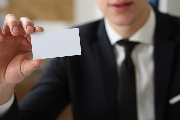 Empresário de terno segurando o cartão de visita