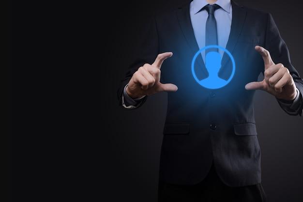 Empresário de terno segurando o ícone de mão do usuário. primeiro plano da interface dos ícones da internet. conceito de mídia de rede global, contato em telas virtuais, espaço de cópia.