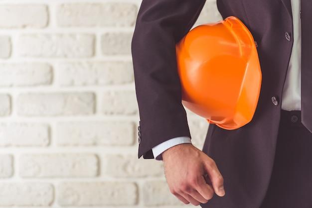 Empresário de terno segurando um capacete