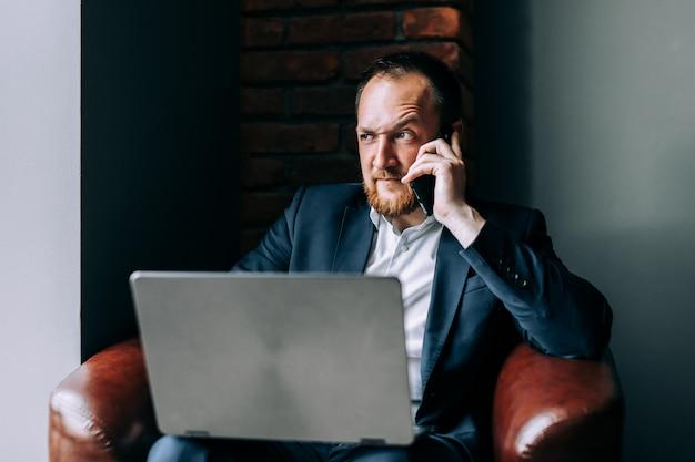 Empresário de terno sentado em uma cadeira com um laptop e falando ao telefone.