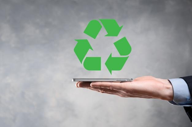 Empresário de terno sobre fundo escuro segurando um ícone de reciclagem