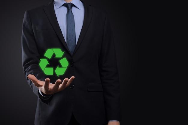 Empresário de terno sobre fundo escuro tem um ícone de reciclagem, cadastre-se em suas mãos. conceito de ecologia, meio ambiente e conservação. luz neon azul vermelha.