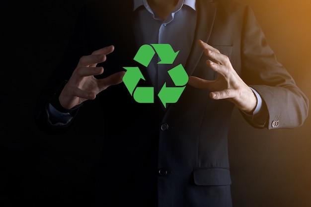 Empresário de terno sobre fundo escuro tem um ícone de reciclagem, cadastre-se em suas mãos.