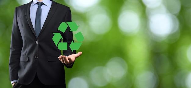 Empresário de terno sobre fundo verde natural segurando um ícone de reciclagem