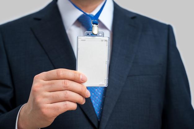 Empresário de terno usando uma etiqueta de identificação em branco ou cartão de visita em um cordão em uma exposição ou conferência.